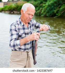 Happy adult man enjoying fishing and removing catch from hook