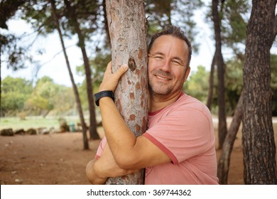 Happy adult man hugging the tree and smiling