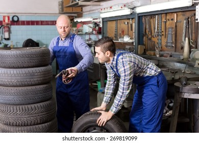 Happy adult mounting specialists working at auto repair shop. Focus on the right man