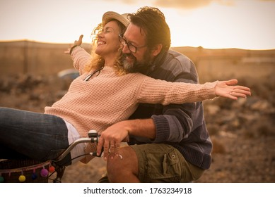 Happy adult people cheerful couple enjoy the outdoor leisure activity riding a bike together man carrying woman and laugh a lot in friendship and relationship - active youthful persons