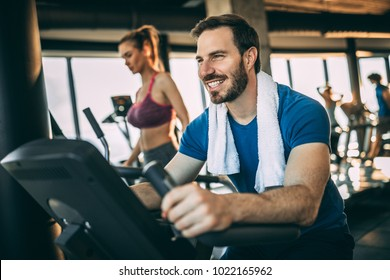 Happy adult person having fun in the gym. Bicycle for better cardio workout.