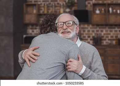 happy adult son and senior father hugging at home