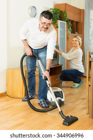 Happy adult spouses dusting and hoovering at domestic interior