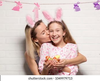 Happy adult woman and child with easter eggs. Family in an Easter suit with rabbit ears