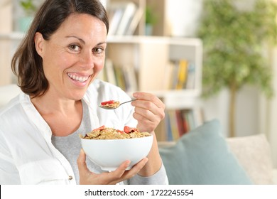 Happy adult woman holding cereal bowl with fruit having breakfast sitting in the sofa at home