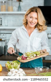 happy adult woman making healthy salad at kitchen and looking at camera