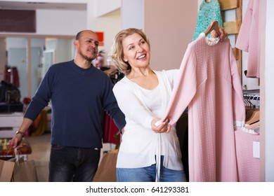 Happy adult woman selecting the dress