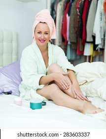 Happy adult woman taking care of leg skin after shower