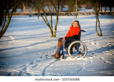 happy adult woman wearing winter clothes on sitting on wheelchair in the snow making snowball