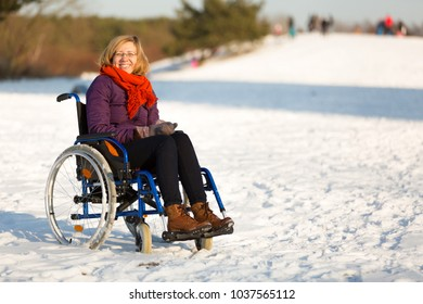 happy adult woman wearing winter clothes on wheelchair in the snow