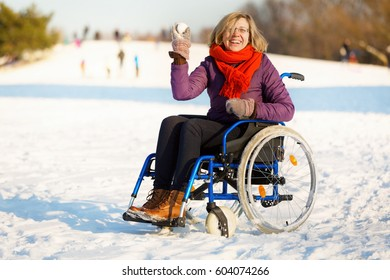 happy adult woman wearing winter clothes on sitting on wheelchair in the snow throwing snowball