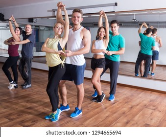 Happy adults dancing bachata together in dance studio