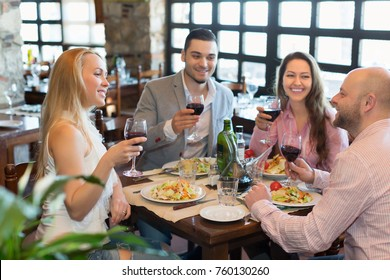 Happy adults having dinner in family restaurant. Focus on blonde girl