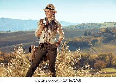 happy adventure solo tourist woman in hiking clothes with bag and retro film photo camera looking into the distance on summer Tuscany trekking.