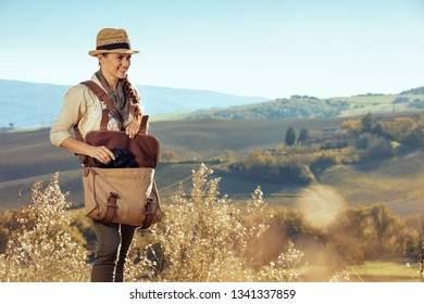 happy adventure woman in hiking gear with bag pulls out binoculars of the bag. summer hiking in Tuscany, Italy.