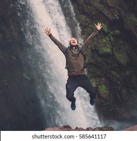 Happy adventurer jumping near Ouzoud waterfall in Morocco.