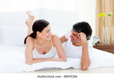 Happy affectionate couple interacting lying on their bed