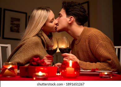 Happy affectionate young couple in love kissing, drinking red wine having romantic dinner date celebrating Valentines day on February 14 or anniversary sitting at table at home or in restaurant.