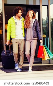 Happy affectionate young couple with luggage and brightly colored shopping bags exiting the entrance to a store onto the sidewalk