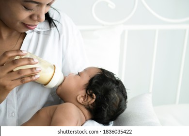 Happy African American baby infant drinking milk form bottle on mother arm. Breastfeeding. Portrait of a cute little baby sucking milk form bottle after wake up happily on mother's arms at home,