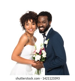 happy african american bride and bridegroom holding bouquet and looking at camera isolated on white