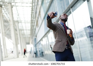 Happy African American business man dances while he listens to the music in his smartphone