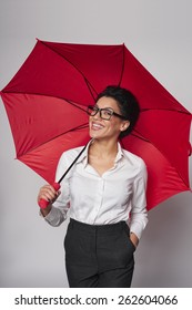 Happy african american business woman standing with red umbrella, over gray background