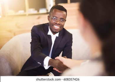 Happy african American businessman handshaking with client or competitor closing deal in an office interior with a wooden background. interview concept
