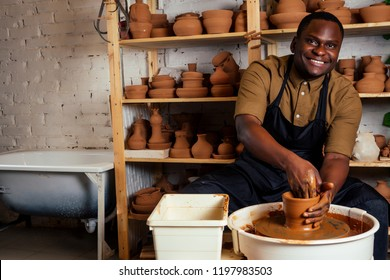 happy African American businessman potter male owner making clay sculpture pot cup vase at workbench in workshop studio . creativity and creative china shop merchant