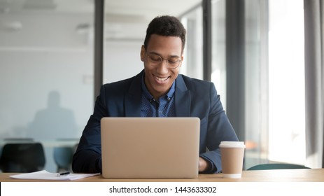 Happy african american businessman wear suit glasses working on online project typing on computer sit at office desk, smiling black male entrepreneur using laptop business corporate apps software