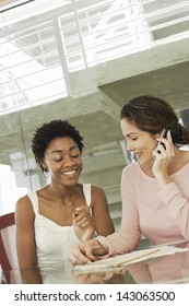 Happy African American businesswoman with female colleague using mobile phone in conference room
