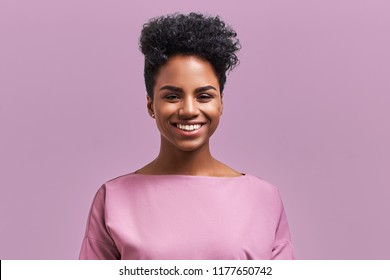 Happy African American businesswoman with positive smile, has crisp dark hair, rejoices having weekend and good rest after hard working exhausting week, isolated on lavender wall.