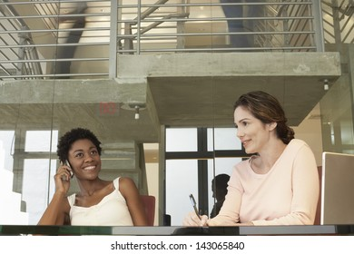 Happy African American businesswoman using mobile phone with female colleague in conference room