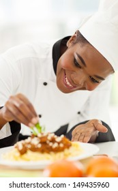 happy african american chef in kitchen decorating pasta dish