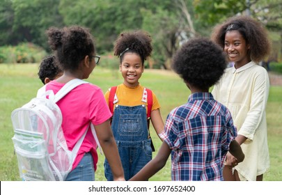 Happy African American childrens standing and holding hands together in circle in the park, Education outdoor concept