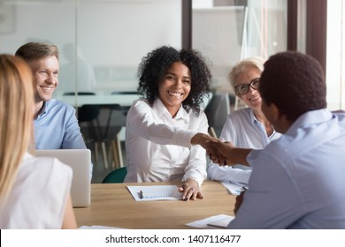 Happy african american colleagues partners handshake at team corporate meeting, mixed race company manager and client shake hands make business deal showing trust respect at diverse group negotiation