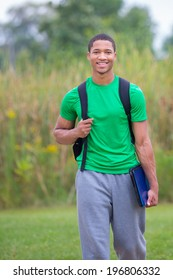 Happy African American College Student Holding Laptop walking outdoor