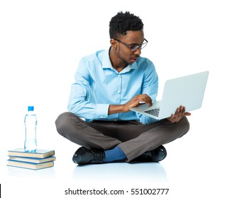 Happy african american college student sitting with laptop on white background