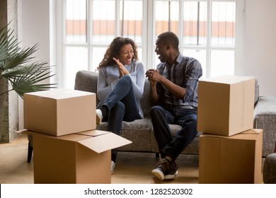 Happy african american couple feeling excited on moving day, black family tenants laughing celebrating relocation sitting on sofa with boxes, home owners having fun in new house together concept
