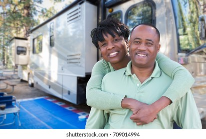 Happy African American Couple In Front of Their Beautiful RV At The Campground.