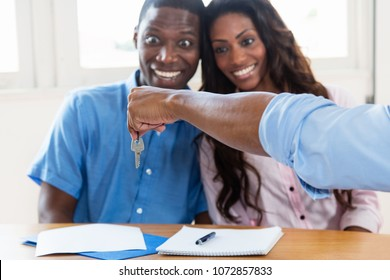 Happy african american couple gets the key for new home from the real estate agent