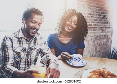 Happy african american couple are having breakfast together in the morning at wooden table.Smiling black man and his girlfriend drinking fresh juice and black coffee on breakfast at at home.Flares