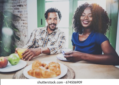 Happy african american couple are having breakfast together in the morning at the wooden table.Smiling black man and his girlfriend drinking fresh juice and black coffee on breakfast at home