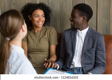 Happy African American couple holding hands looking at each other, being reconciled after successful psychology treatment, happy black lovers make peace in therapist office. Saved marriage concept