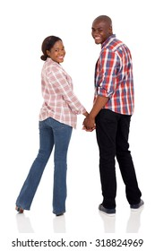 happy african american couple holding hands and looking back isolated on white
