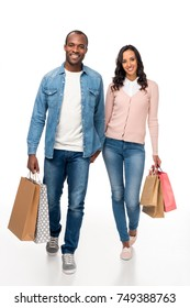 happy african american couple holding shopping bags and smiling at camera isolated on white