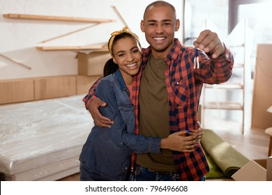 happy african american couple holding keys in new apartment