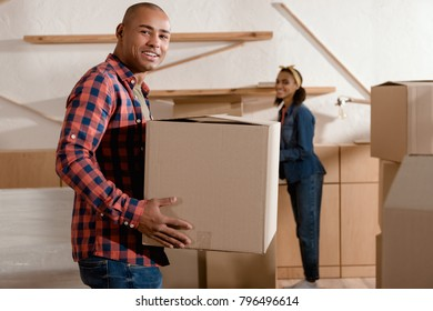 happy african american couple holding cardboard box and moving to new apartment