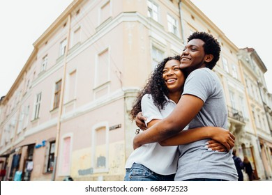 Happy african american couple hugging and kissing over old city background in summer time. Love, holiday, travel and relationship concept