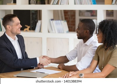 Happy African American couple meeting handshake Caucasian real estate agent ready to sign rent contract, excited black husband and wife shake hand counselling with broker or realtor in office